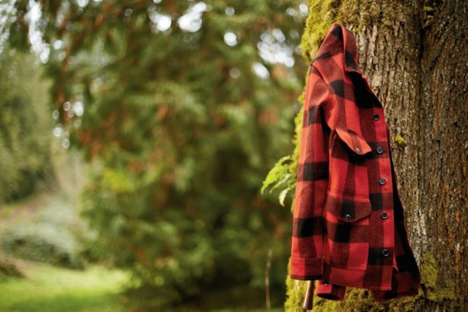 red and black plaid coat hangs on a tree branch
