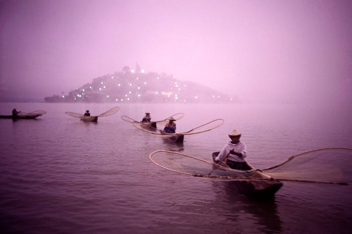 curving line of fishermen with single man boats and fishing nets in front of lighted island