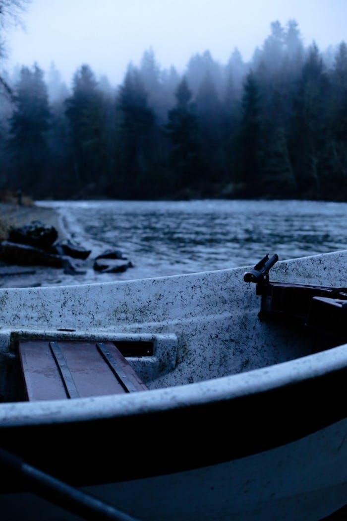 boat in lake with foggy pine treeline backdrop
