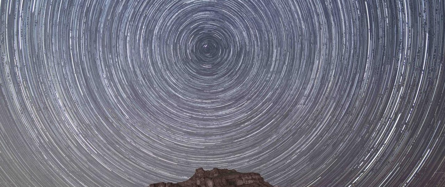 long exposure shot of circular star trails above rocky mountain