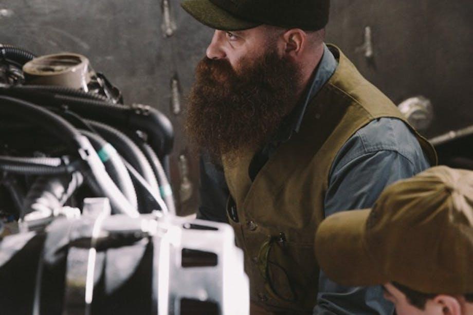 sitting bearded man with filson vest and short billed felt cap