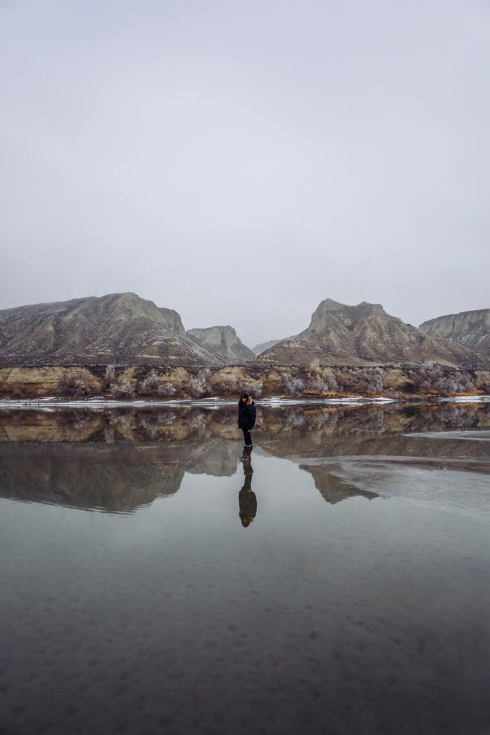 Tyson Edwards; Standing on a reflective body of shallow water with rocky mountains