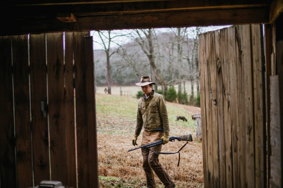 man walks toward barn door from outside with shotgun and stetson hat