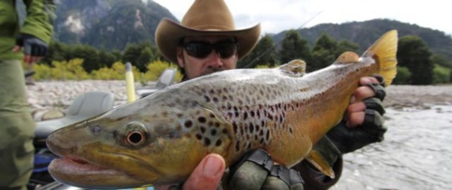 Man with cowboy hat holds fish up to camera on river with mountain background