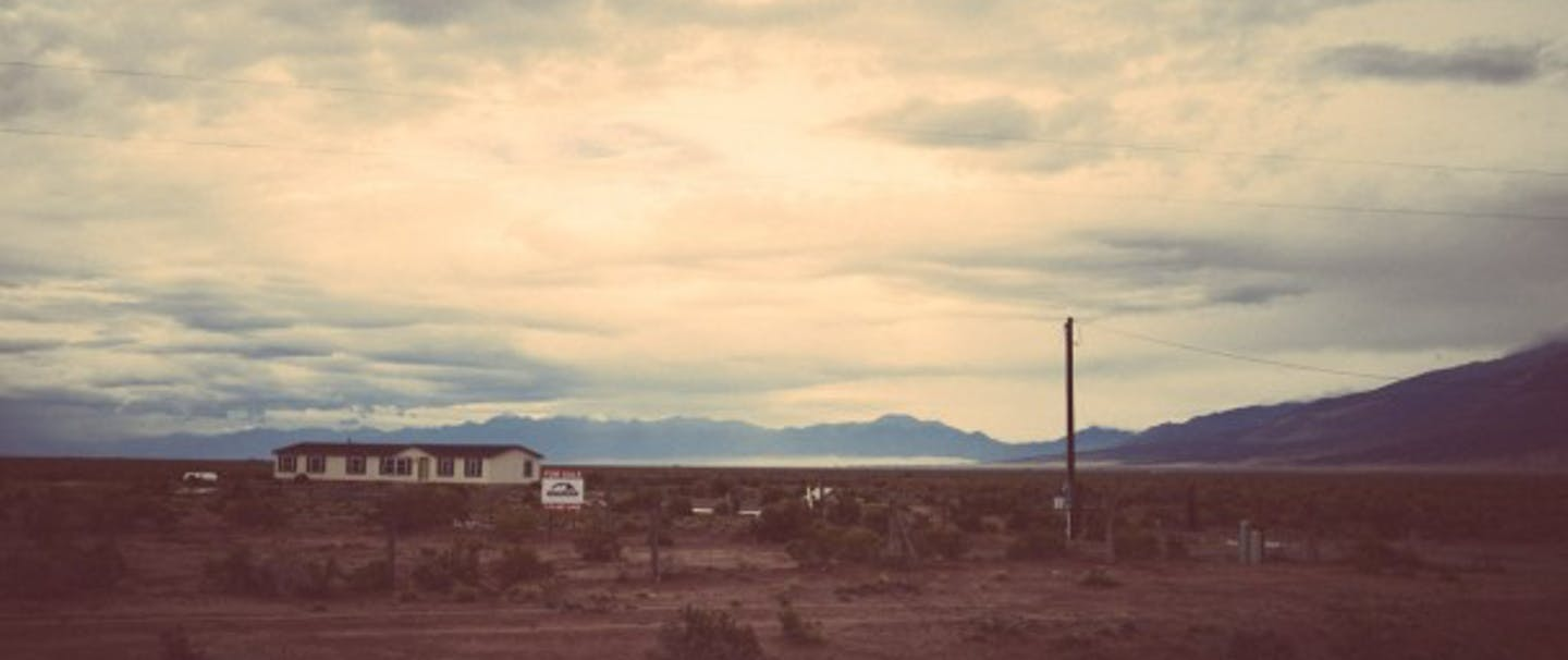 house in desolate desert landscape with large mountains in background and big open sky
