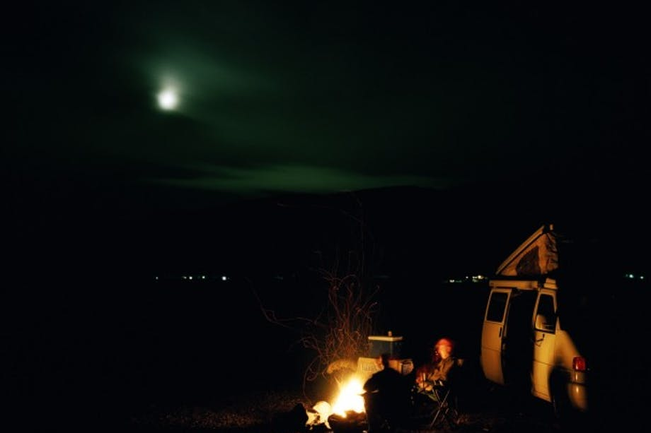 camper van lit by the light of fire with the moon in the sky