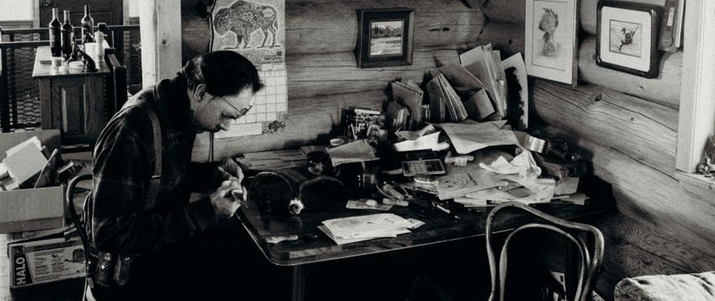 john working at his desk in log cabin with antler chandelier