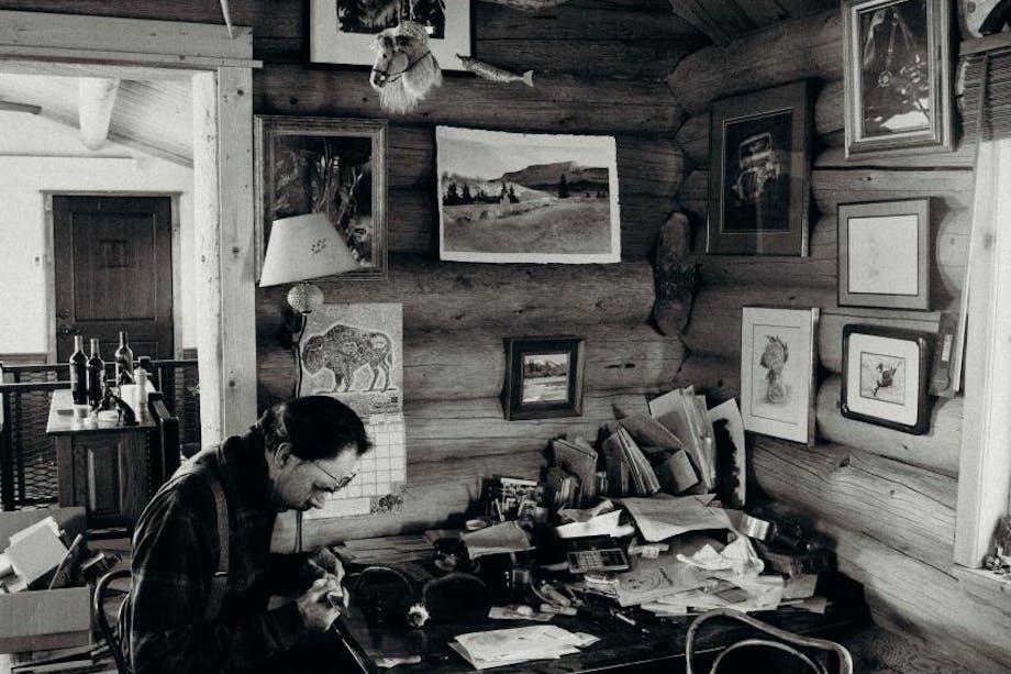 john working at his desk in log cabin with antler chandelier
