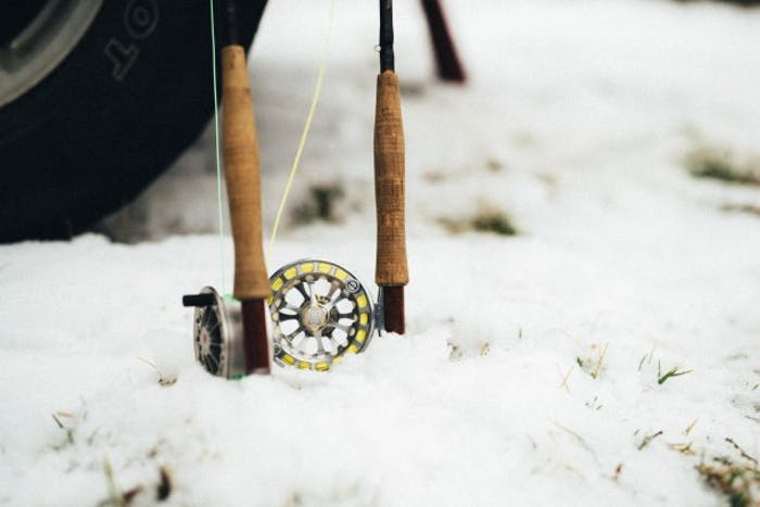 two fly fishing rods and spools protruding out of snow