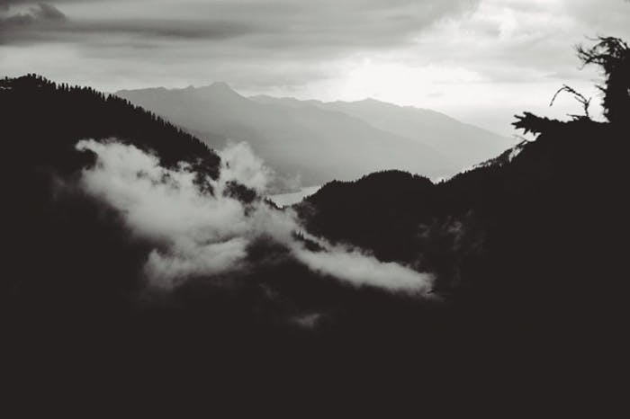 Black and white alpine hills and clouds with river and mountains in background
