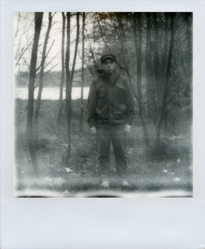 George barnett black and white polaroid of man standing in front of woodland lake