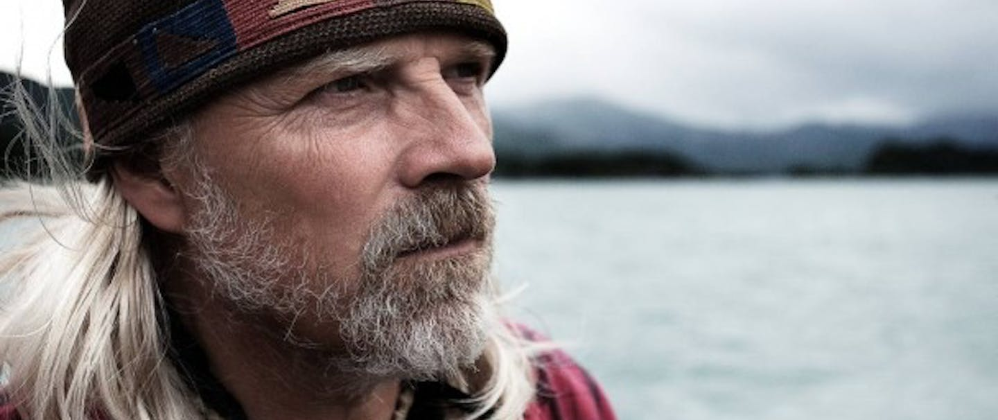 Lee Kjos with long white hair in brown fabric hat and red plaid shirt on the water in a lake