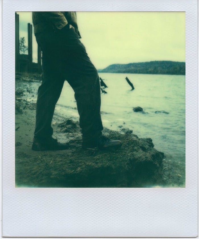 polaroid of man standing at edge of large body of water