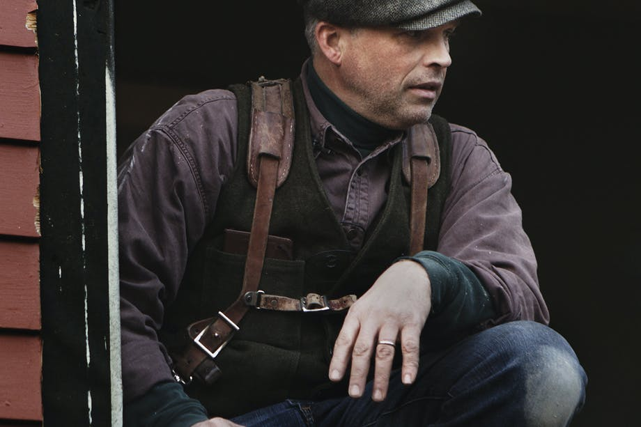 Daniel Westbrook kneels with grey newsboy cap, black vest, purple buttonup and leather holster straps