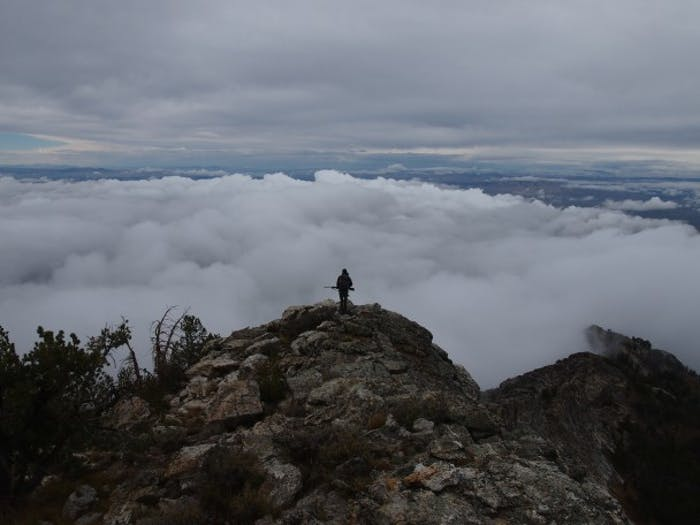 Snowcock Hunting; hunter stands on mountaintop above the clouds
