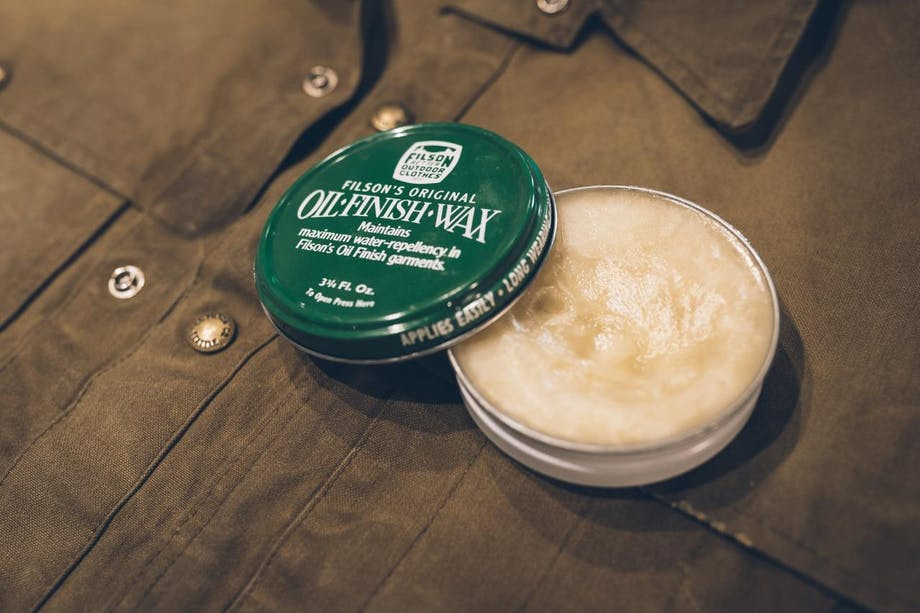 green tin of filson oil finish wax sits on top of brown jacket