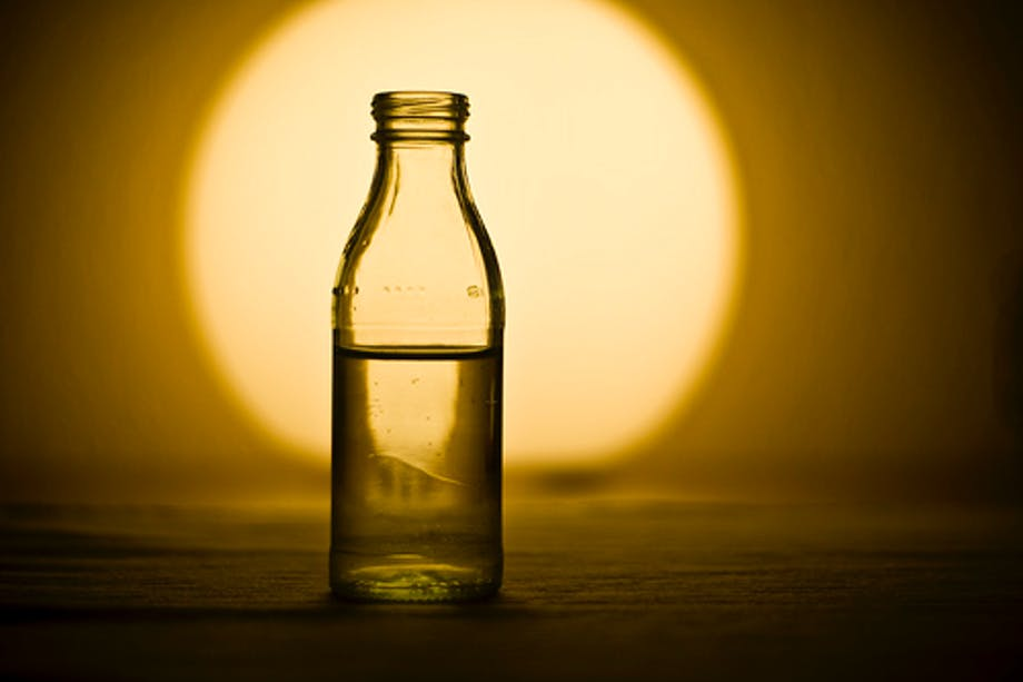 bottle of water in front of a glowing orb of light