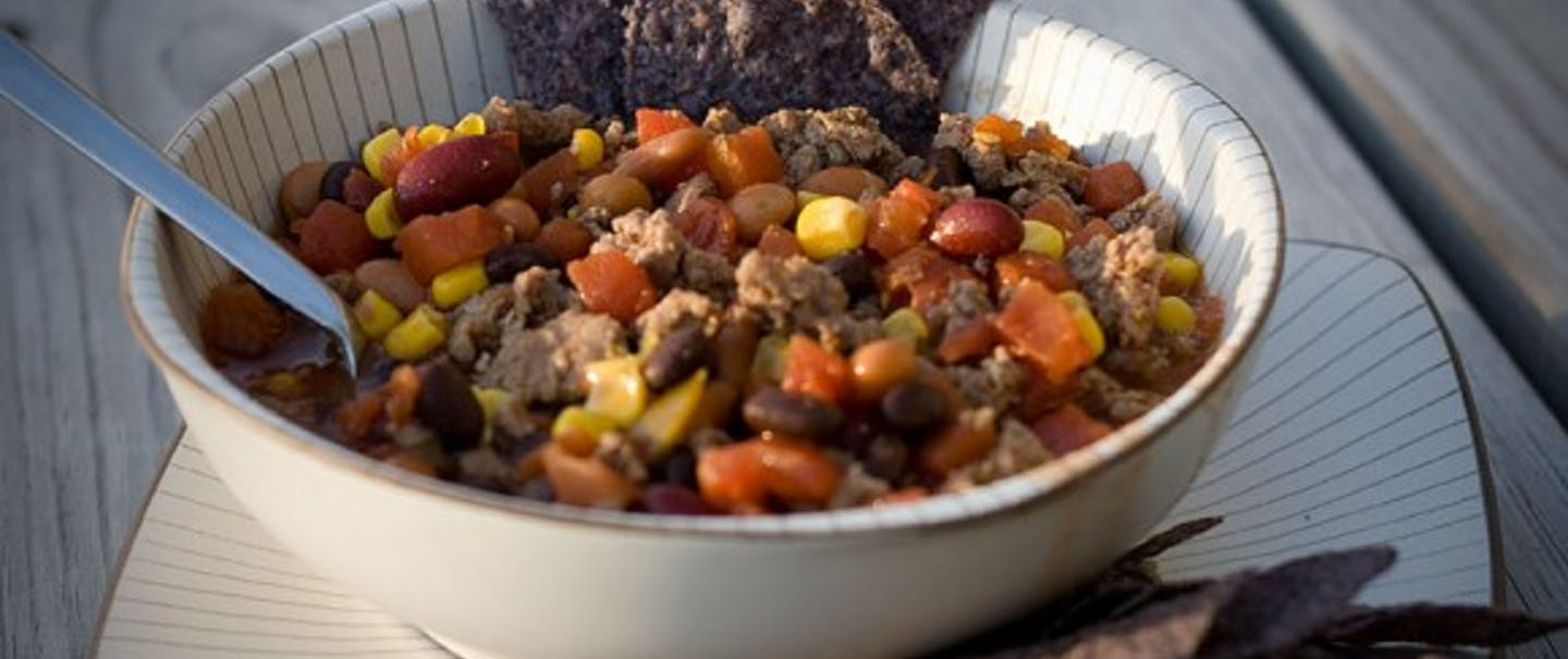 bowl of southwest venison chili and blue corn tortilla chips
