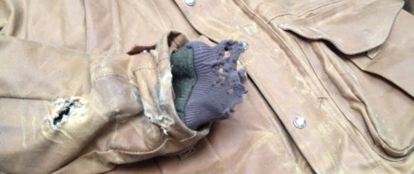 partially ripped tin cloth motorcycle jacket shows the results of a crash