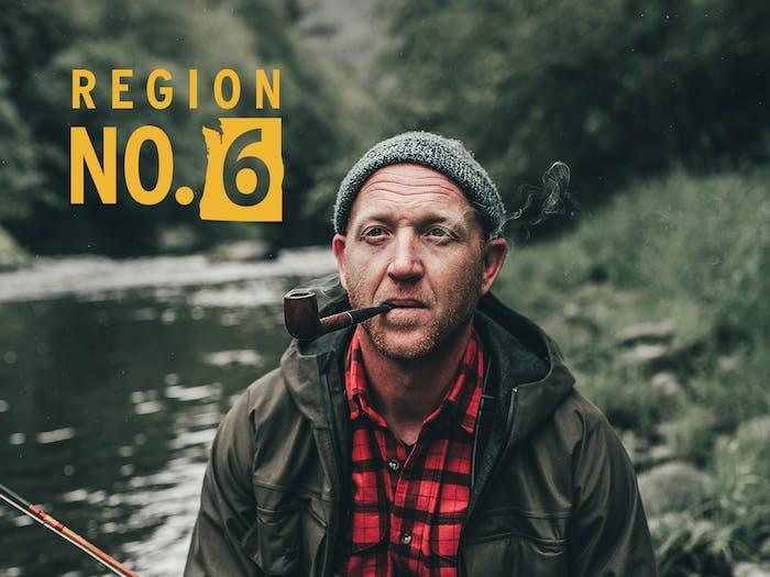 fly fisherman standing on river bank wearing filson coat smoking pipe