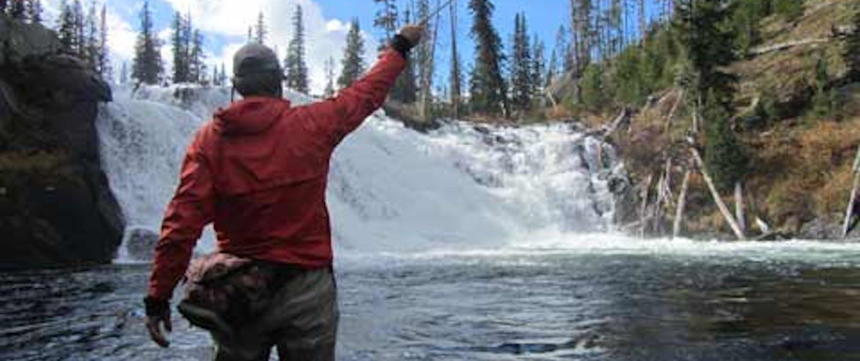 man fly-fishing at base of waterfall