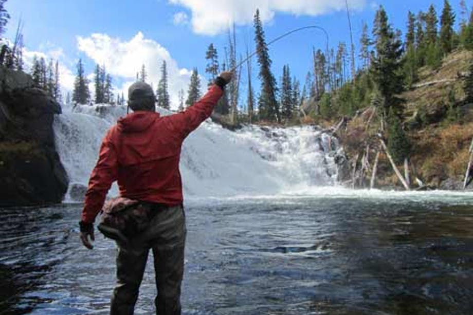 man fly-fishing at base of waterfall