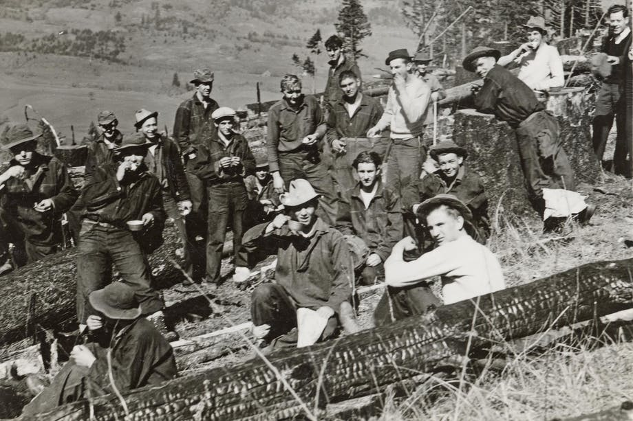 historic image of men sitting down to eat lunch in field among burned trees
