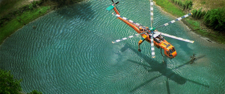 orange helicopter flying over pond