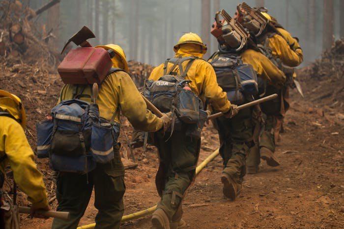 hotshots walking through dirt path in forest carrying their gear to location