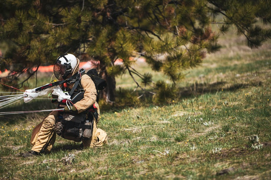 smokejumper firefighter safely landing from practice jump in grassy field