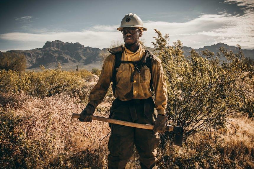 hotshot fireman holding hoe in grassy field