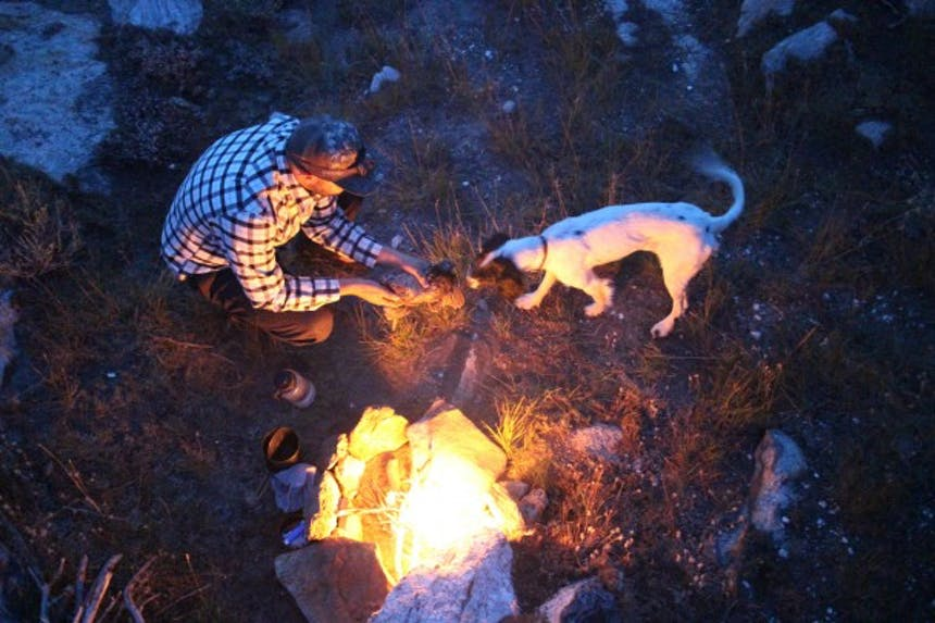 man prepping bird to cook over campfire with dog