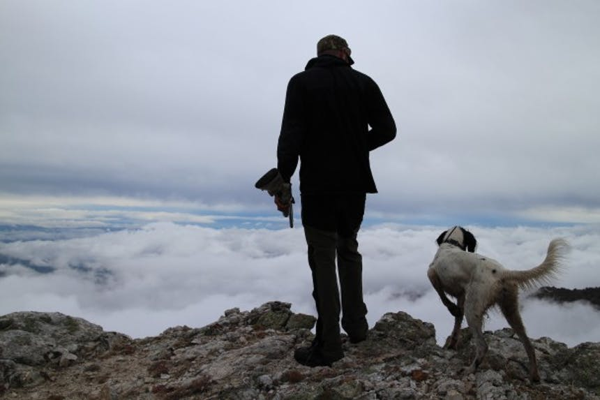 Man hunting with his dog on rocky ridge looking down into clouds