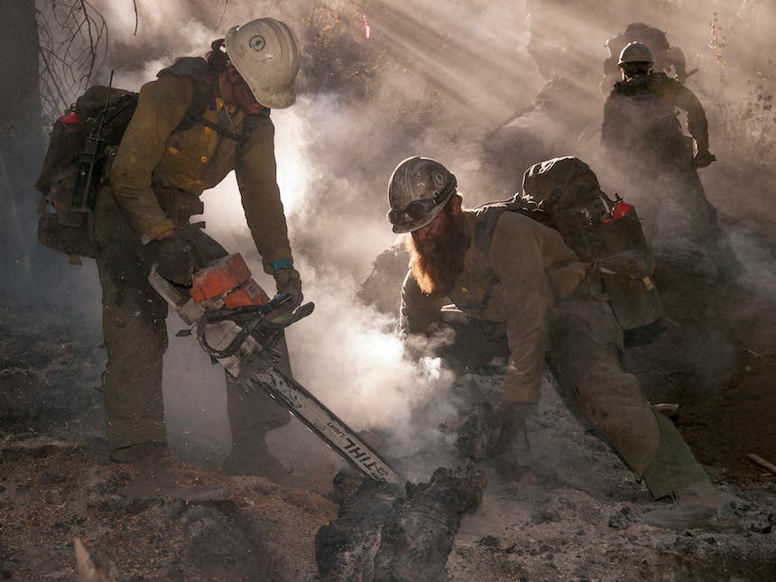 firefighters cutting charred log in smoky forest