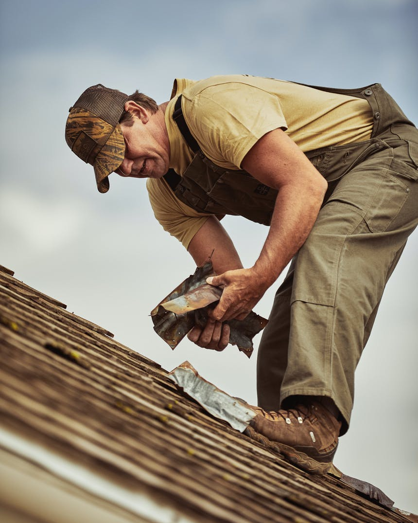 man cleaning up scraps from roofing