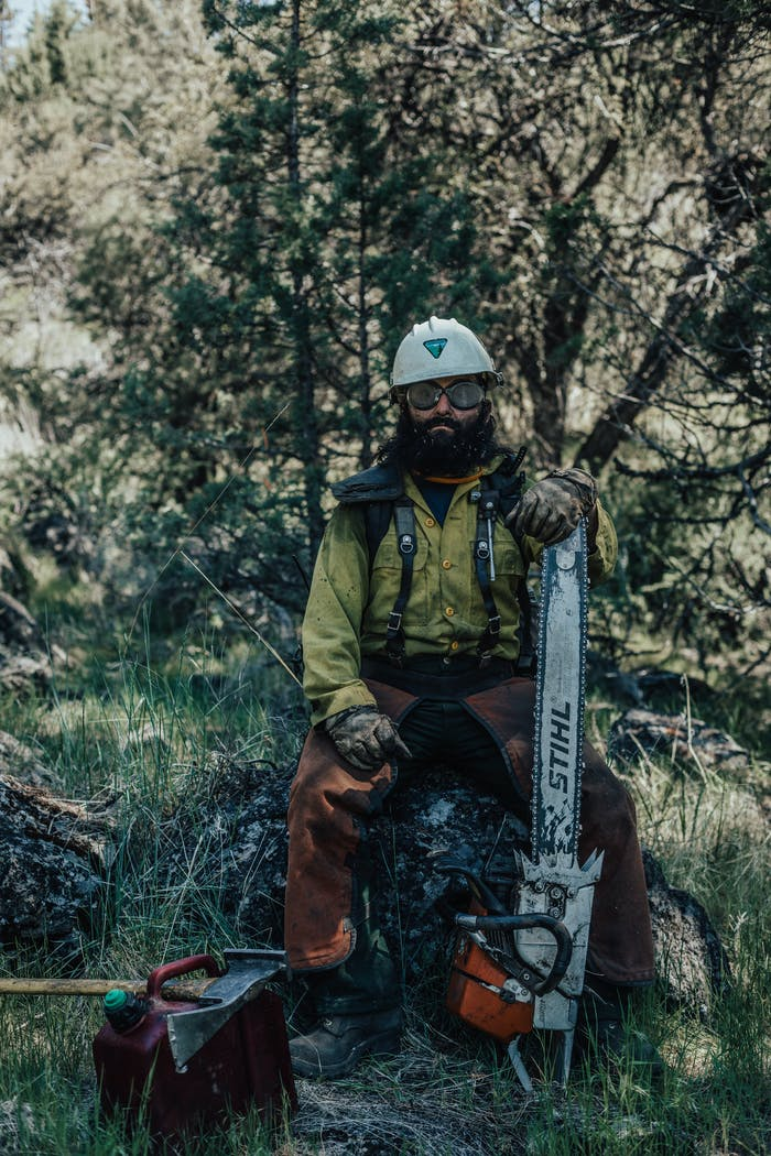 veterans hot shot crew member sitting on rock with chainsaw