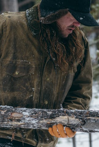man with long brown hair wearing brown jacket, tan gloves and winter cap carrying a log in the woods with snow on the ground