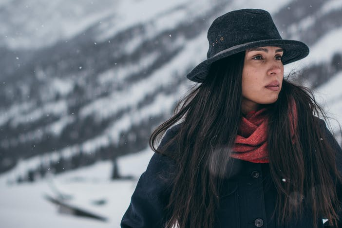 Native American woman wearing black wool coat, red scarf and black packer hat looking to the right with snowy mountains blurred behind her