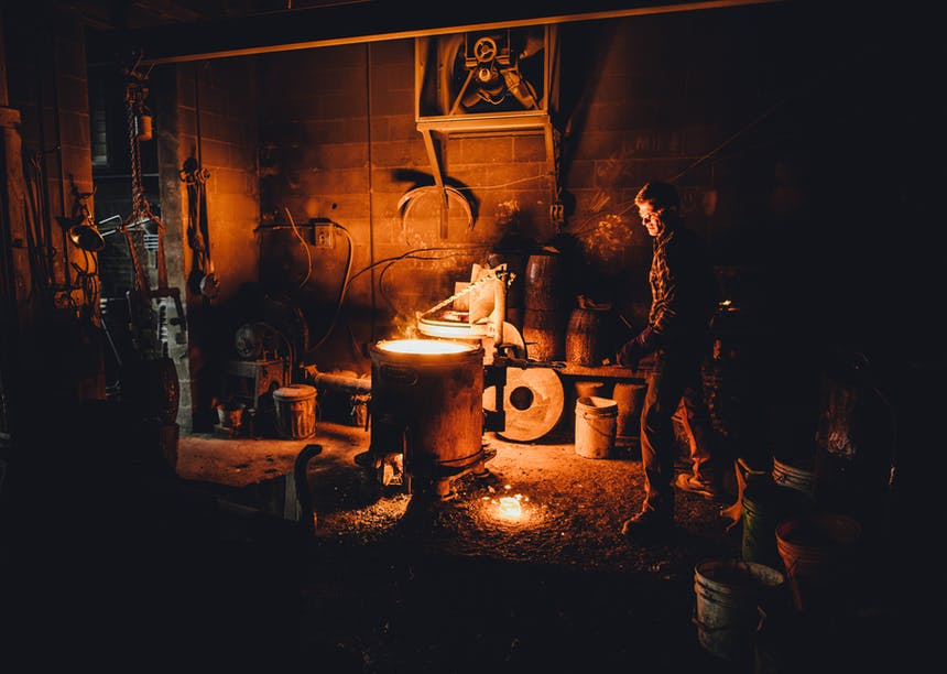 man working with hot metal in foundry at night