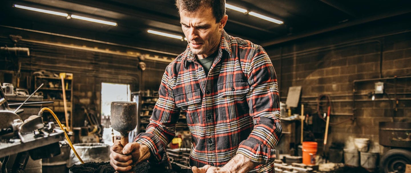 man wearing red and black flannel working in foundry