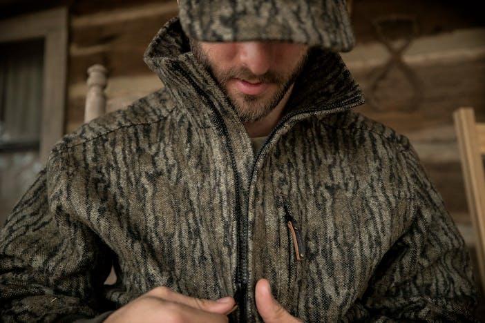man zipping up camo jacket