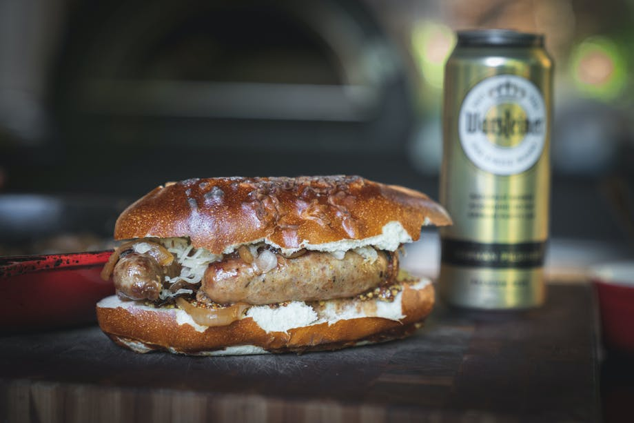 beer brat in bun next to beer