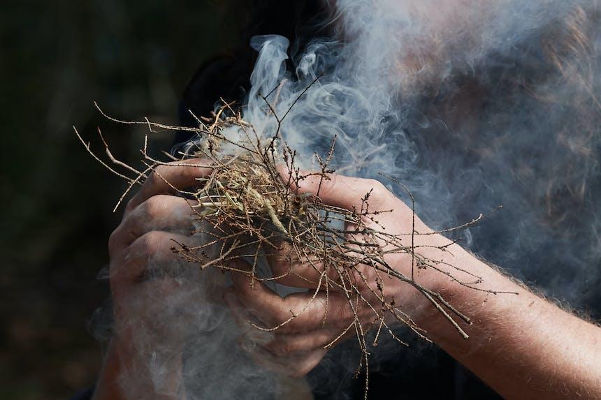 smoking twigs as man starts fire