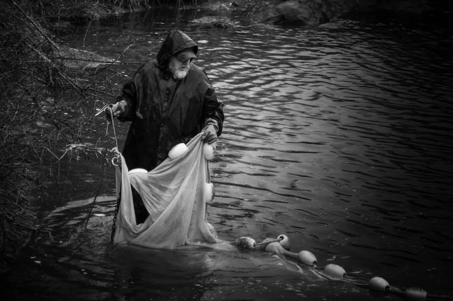 man moving fishing net in river