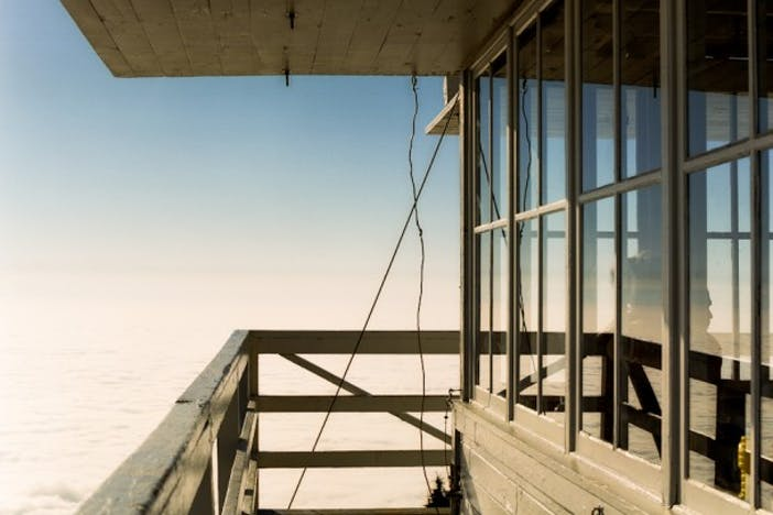 the view from the exterior of the lookout on the wrap around deck, blue sky and clouds below