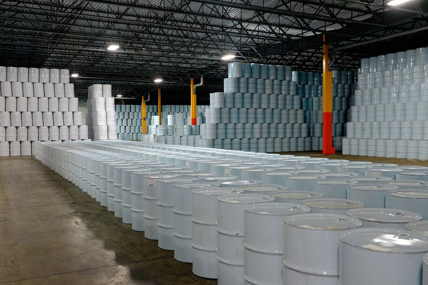 warehouse full of white maple syrup barrels stacked to the ceiling in along the walls