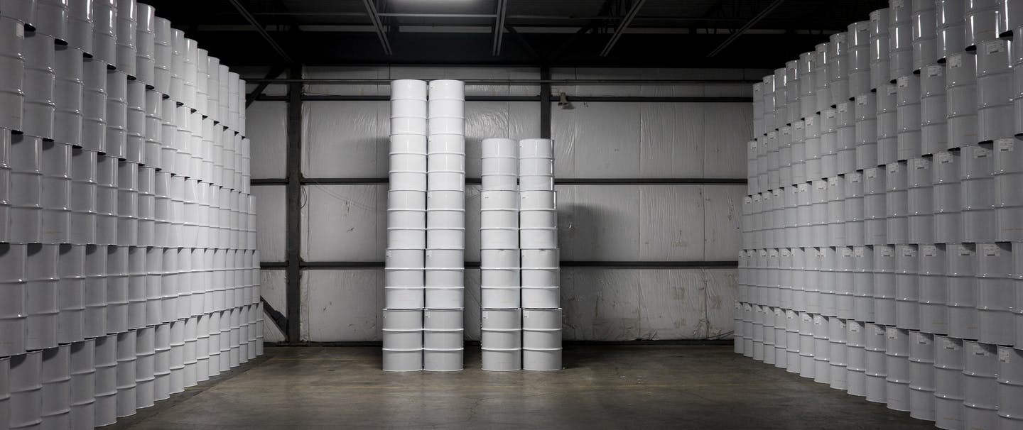 warehouse of white maple syrup barrels stacked to the ceiling on the right and left