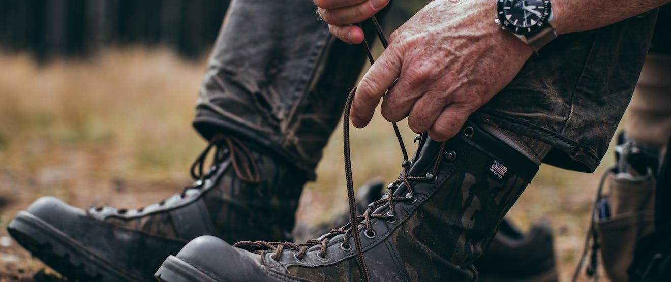 man lacing up his boots