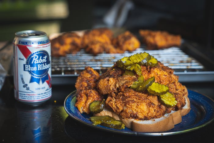 fried chicken with pickles on top of bread with a beer