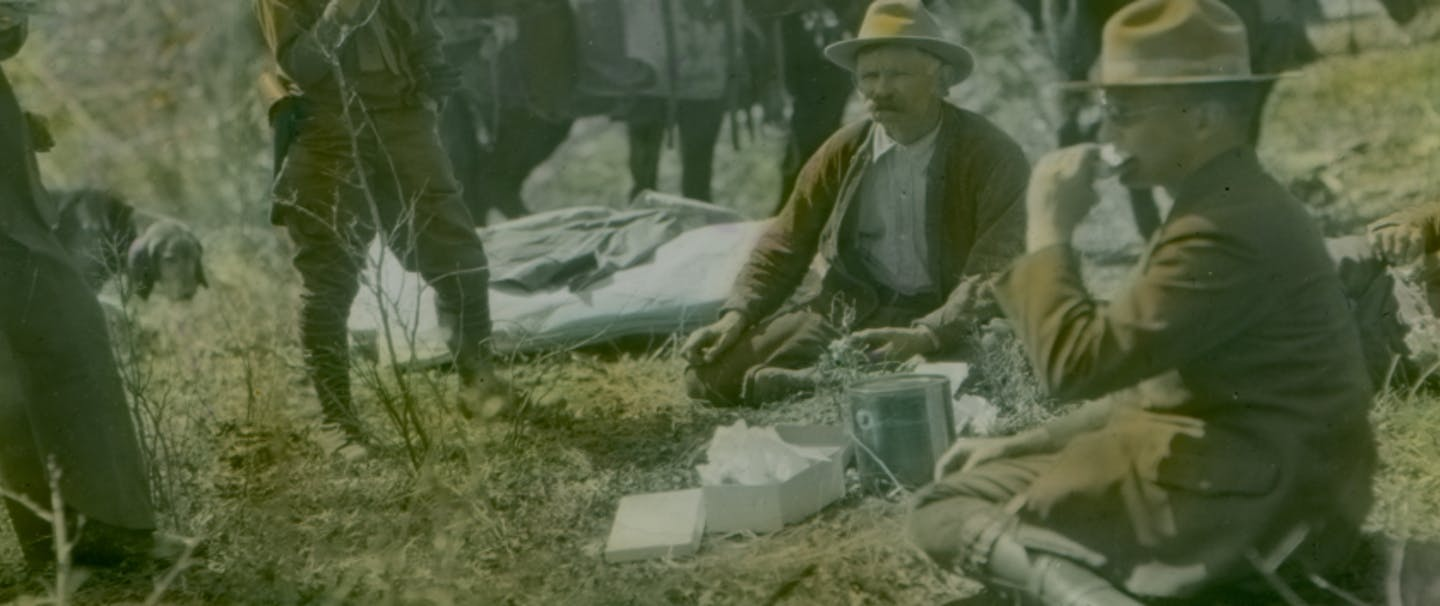 historic photo of forest service men sitting down to eat lunch in their uniforms